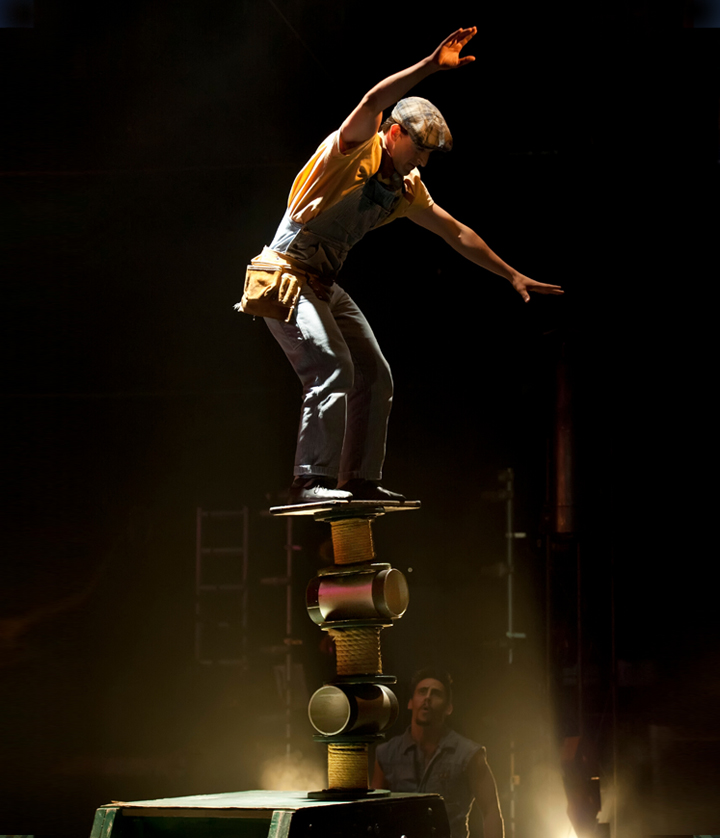 Man balancing on stack of cylinders in circus stage show Birdhouse Factory