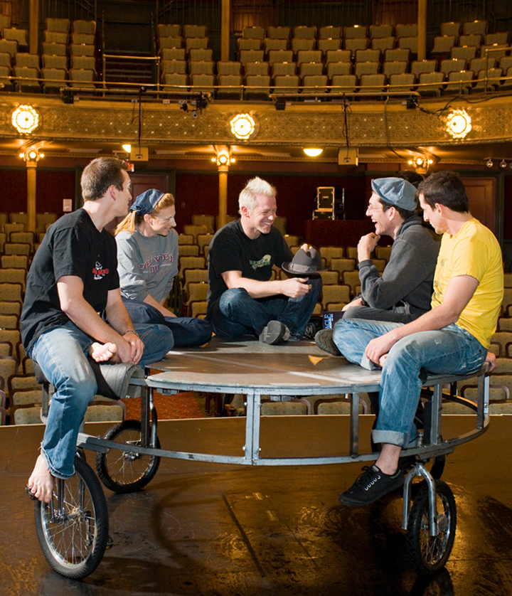 Cast of Cirque Mechanics Birdhouse Factory seated on Spin Cycle device at the New Victory Theater in New York